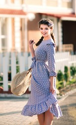 A beautiful smiling woman in a blue pea dress walks in the city street. Happy sincere summer outdoor portrait of attractive model
