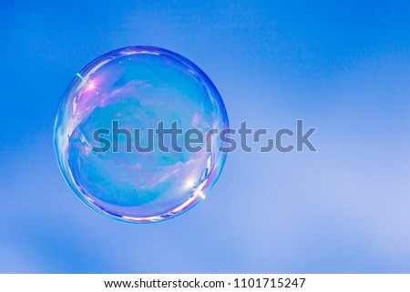 A beautiful soap bubble against blue sky.