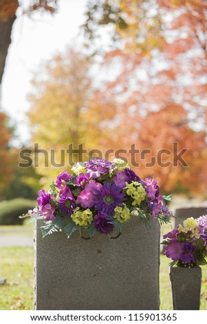 A beautiful spray of purple flowers grace the top of a tombstone in the fall.