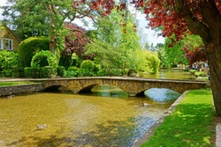 A beautiful summer day showing the River Windrush flowing through Bourton on the Water, also known as The Venice of the Cotswolds, Gloucestershire, England, United Kingdom