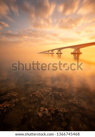 A beautiful sunrise at the Zeeland Bridge. The Zeeland bridge is the longest bridge in Zeeland and is connecting 2 islands. It was a beautiful sunrise, in the foreground you see rocks with oysters.  #1366745468