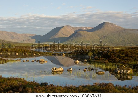 A beautiful sunrise on Rannoch Moor in Scotland with a great view over the so-called Black Mount, reflected in Loch Nah-Achlaise.