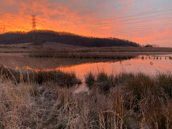 A beautiful sunrise rises up behind the hills at Gupton Wetlands, Swan Pond Recreation Area, Roane County, Tennessee on a late February frosty morning.