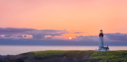 A beautiful sunset forms as the sun set below the horizon of the ocean with a lighthouse overlooking the grassy headlands of the coastline.