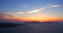 A beautiful sunset from Fira, Santorini Greece. This Santorini sunset is over the caldera to the setting sun. Santorini is famous for its sunsets. Fira, Santorini, sunset, night sky, pretty red clouds