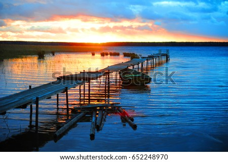 Stock Photo A beautiful sunset on a deserted pier at the lake.