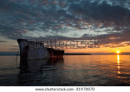 A beautiful sunset over a rusty freighter acting as a breakwater for a harbor - Powell River, British Columbia, Canada.