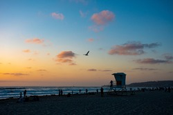 A beautiful sunset over the ocean off the California coast. Beach goers and a life guard stand in view.