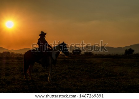 A beautiful sunset silhouette of cowboys riding horseback with mountain range background during golden hours on the field  #1467269891