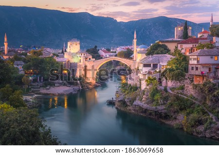 A beautiful sunset view of the iconic Stari Most bridge, Neretva River and old town of Mostar, Bosnia and Herzegovina with mountain backdrop. Stock fotó ©