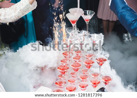 A beautiful table setting with empty or full glasses of wine or champagne that stand on top of each other as a slide or triangle on a dark background in the interior of a cafe and restaurant.