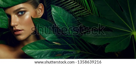 A beautiful tanned girl with natural make-up and wet hair stands in the jungle among exotic plants. #1358639216