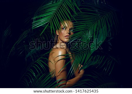 A beautiful tanned girl with natural make-up and wet hair stands in the jungle among exotic plants #1417625435