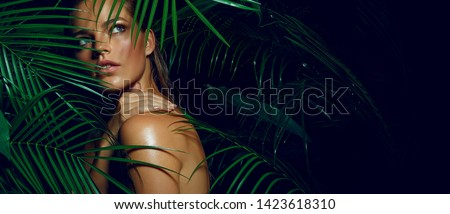 A beautiful tanned girl with natural make-up and wet hair stands in the jungle among exotic plants #1423618310