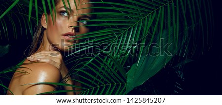 A beautiful tanned girl with natural make-up and wet hair stands in the jungle among exotic plants #1425845207
