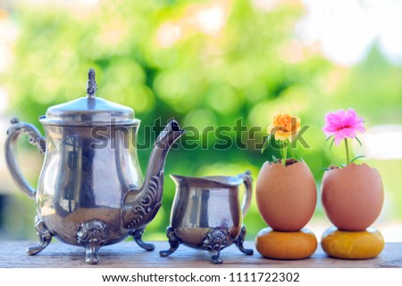 A beautiful teapot and teacup with yellow and pink moss rose in egg shell on wooden board with nature background. #1111722302