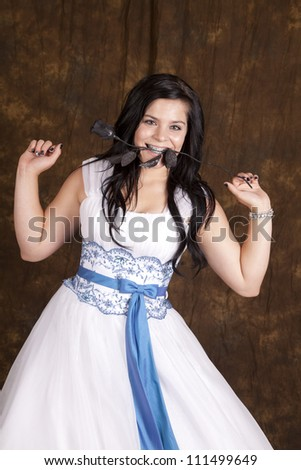 A beautiful teen girl in her formal dress holding on to a black rose in her mouth.