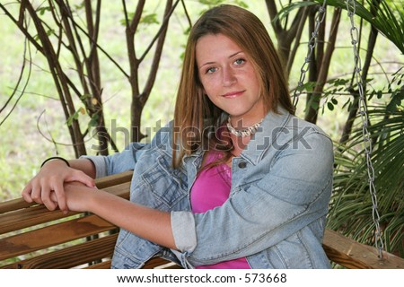 stock photo : A beautiful teen girl sitting on a porch swing in the shade.