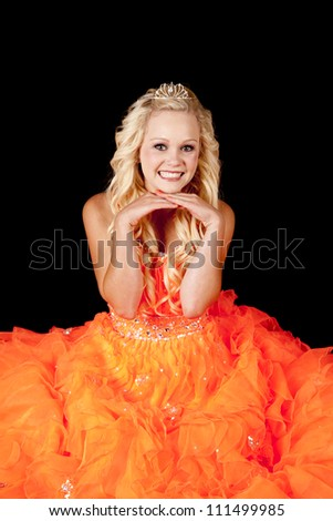 a beautiful teen in her bright orange dress playing princess with her crown.
