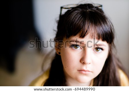 A beautiful teenage girl with a nose piercing and glasses looking into the camera with copy space on the left. #694489990