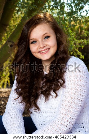 Stock Photo A beautiful teenage girl with big, blue eyes, dimples, and brown hair poses for a portrait.