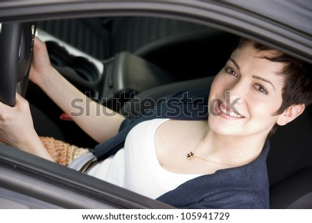 A beautiful thirty something woman holds the steering wheel female driver