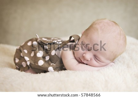 A beautiful three week old baby girl sleeping, soft focus