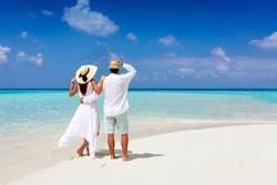 A beautiful tourist couple in white summer clothes and hats stands on a tropical beach and gazes at the turquoise ocean during their vacation time