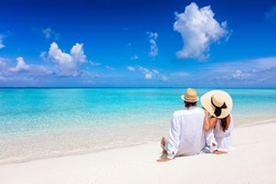 A beautiful tourist couple with hats sits on a tropical beach and enjoys the view to the turquoise ocean during their summer holiday