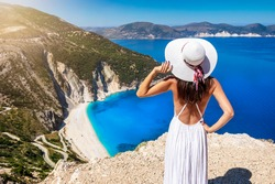 A beautiful tourist woman in white dress and sunhat enjoys the view to the famous Myrtos Beach on the island of Kefalonia, Ionian Sea, Greece
