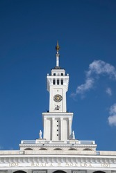 A beautiful tower with a clock and a star on the spire. Blue sky. Old Soviet architecture. Gold star on the spire of the building. Sunny day.