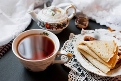 A beautiful version of Breakfast with a white porcelain Cup and a painted teapot in the background, ready-made pancakes on a saucer. Table setting for the Russian holiday Maslenitsa