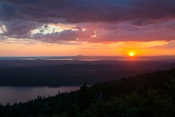 A beautiful, vibrant sunset over Cadillac Mountain in Acadia National Park in Bar Harbor, Maine, on a humid summer day