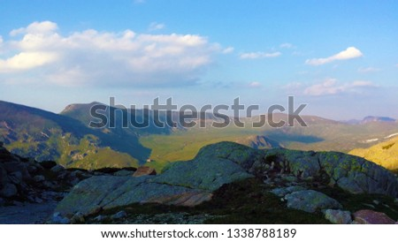 A beautiful view high up in the mountain. You can see rocks, broad green valleys, white clouds on the blue sky.  The photo is taken on a summer sunny July day, in mount Stara Planina, Bulgaria, Europe