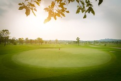A beautiful view landscape in morning time green grass at golf course ,big trees, sand bunker and mist with sunlight rays background.