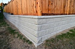 A beautiful view of a corner section of gray block retaining wall with a fence build behind