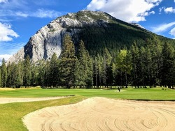 A beautiful view of a huge fairway bunker , with the fairway behind it, with tall trees and a beautiful mountain in the background, in Banff, Alberta, Canada
