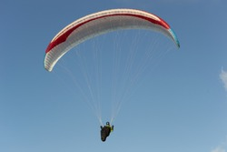 A beautiful view of a paraglide flying gliding on a clear blue sky at the golden hour with a nice wind windy breeze on a sunny day