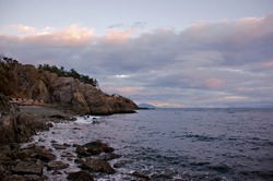 A beautiful view of first light illuminating rugged coastline with cliffs and rocky beach filled with driftwood