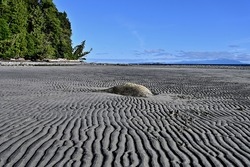 A beautiful view of following the pattern of ripples formed in the sand leading up to a single boulder rock during low tide