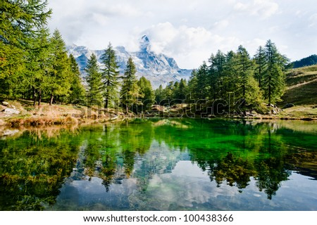 "A beautiful view of ""Lake Blue"", a high altitude alpine lake near Breuil-Cervinia. Evergreen pines are reflected in the tranquil waters of the lake like also the peaks of Mount Cervino-Matterhorn."