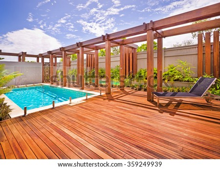 A beautiful view of pool in house in  a sunny day  with wooden floor with a bench
