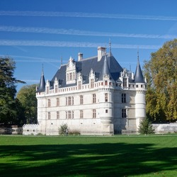 A beautiful view of the famous french castle of Azay-le-Rideau surrounded by a lawn, during a sunny autumn afternoon