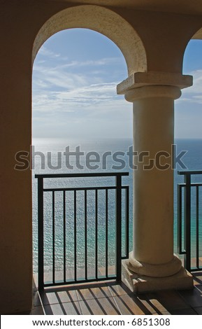 A beautiful view of the ocean through the arches of a balcony.