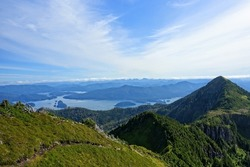 A beautiful view of the scenic ocean and forested mountains from on the top of mount raymond, on the sleeping beauty trail in Haida Gwaii, British Columbia, Canada