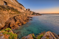 A beautiful view of the town at the sea with rocks and a colorful sunset - Saint Malo, Brittany, France