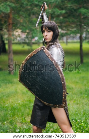Stock Photo A beautiful warrior girl in a chain mail, a sword and a shield in her hand. A woman with long black hair in the image of an Amazon, a Viking. Fantasy. Medieval armor