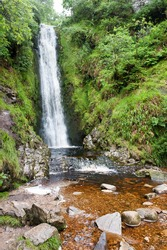 A beautiful waterfall in the  summer time in the forest