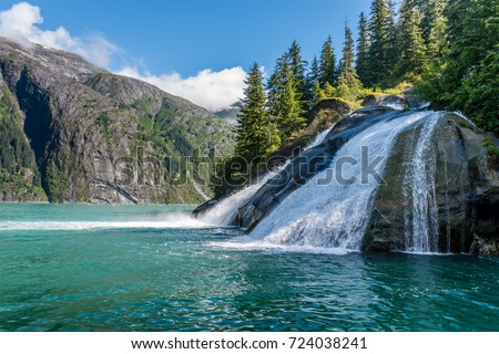 A beautiful waterfall pours massive amounts of water into the sea along Tracy Arm Fjord in Alaska.