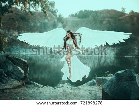 A beautiful white archangel descended from heaven. A girl in a sexy suit with huge white wings. Artistic Photography #721898278